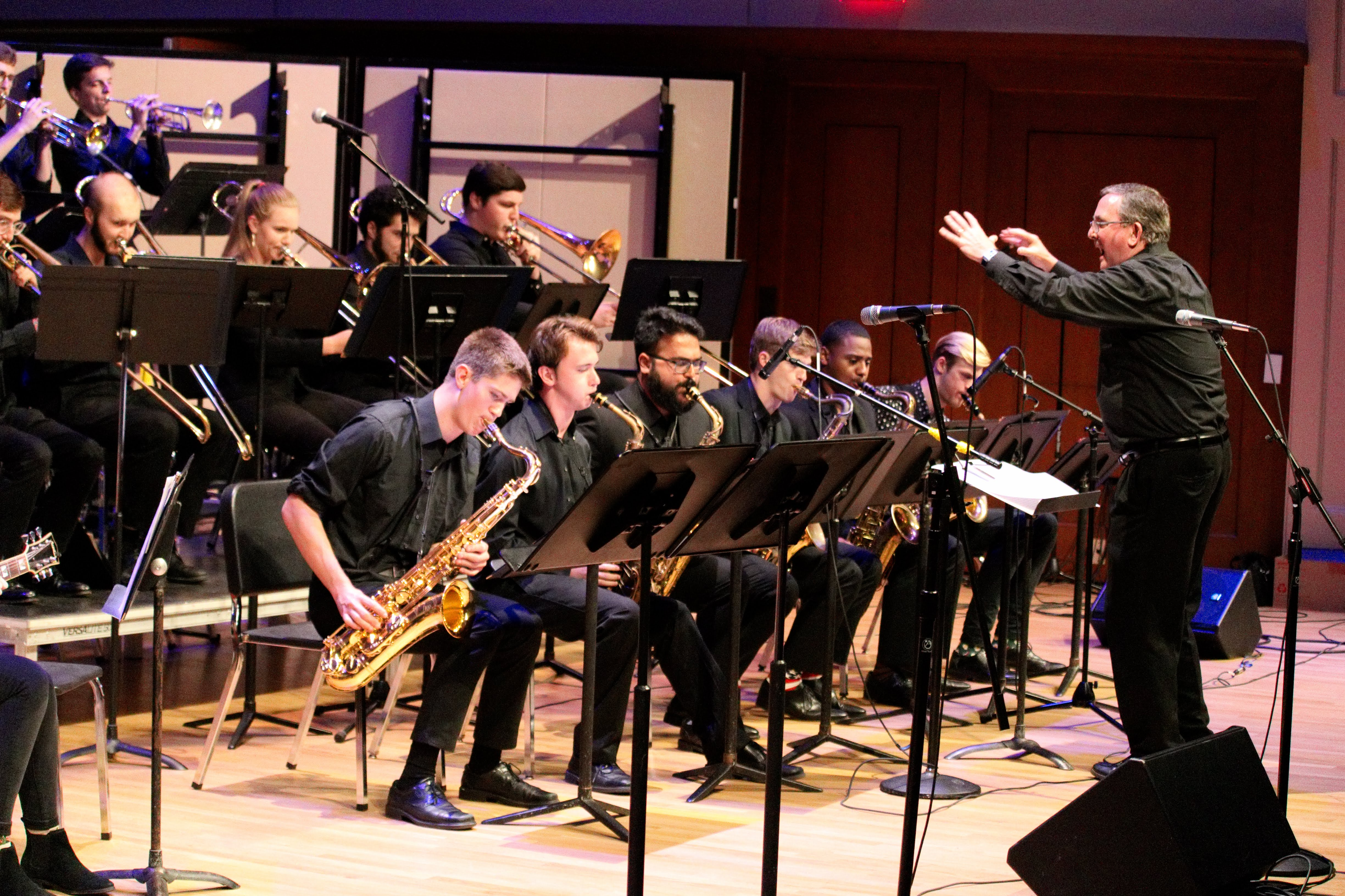 Jim Ketch conducts the Jazz Band with arms outstretched on Moeser Auditorium stage.