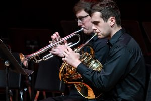 Two students playing trombone and french horn