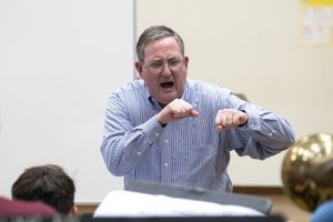 Jim Ketch punches with both hands while directing a rehearsal of the UNC Jazz Ensemble.