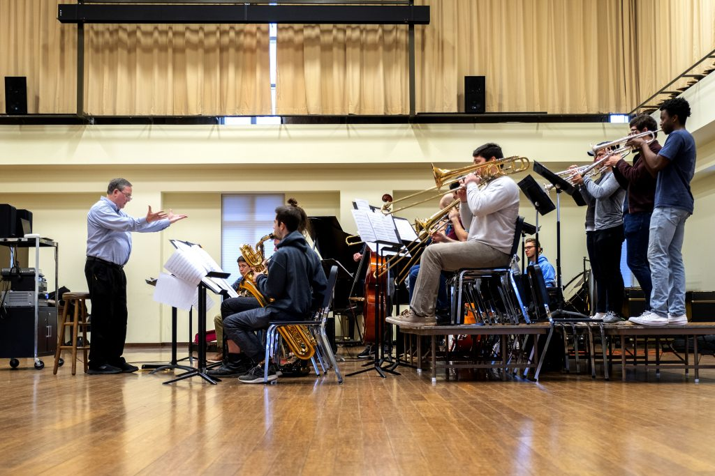 Jim Ketch raises his hands as he directs a rehearsal of the 15-student UNC Jazz Ensemble.