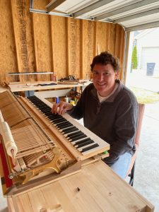 Max poses with a piano deconstructed for maintenance in his home workshop.