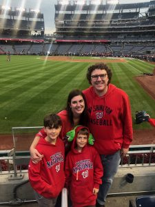 Max with his wife and two boys pose beside the field in the Washington Nationals baseball stadium.