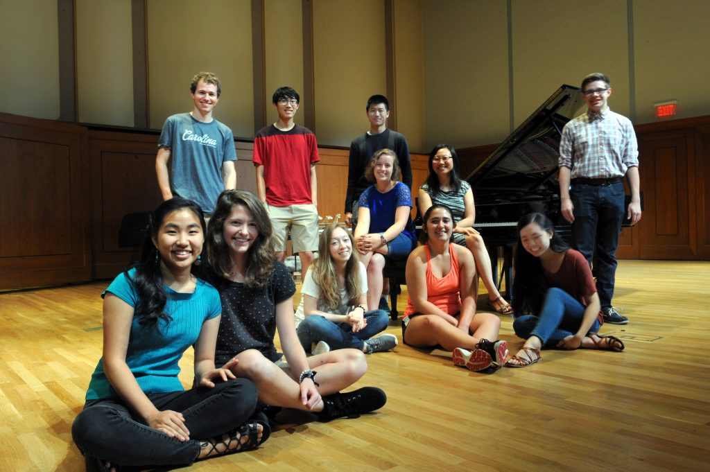 A group of smiling piano students gathered in front of the piano on Moeser Auditorium stage.