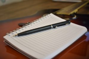 A notebook open to a blank page with a pen on top of it lays on a guitar.