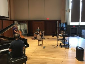 Masked musicians rehearse on Moeser Auditorium stage.
