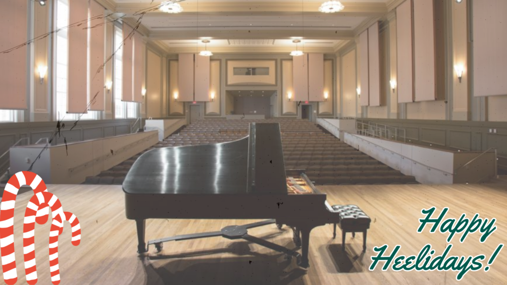 Moeser Auditorium from the stage, looking out at the empty auditorium past the piano on stage. Candy canes and Happy Heelidays! are overlaid.