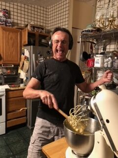 Gene Galvin rocks out as he bakes at home in his kitchen.