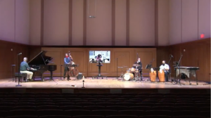 Jazz faculty perform on stage together, masked and socially distanced with saxophonist Barber playing along on a video screen from Hill Hall 103.