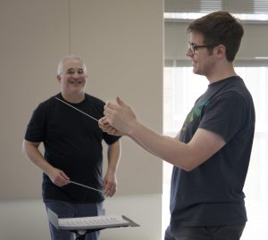 Feldman smiles as student practices conducting
