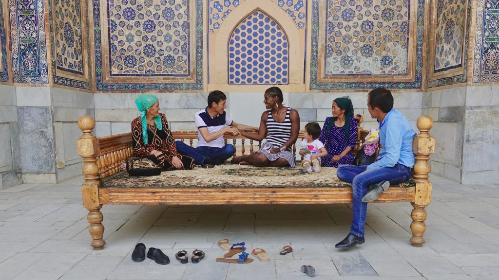 A diverse group of individuals sit and converse on a big bench in front of an ornate wall mural in Uzbekistan.