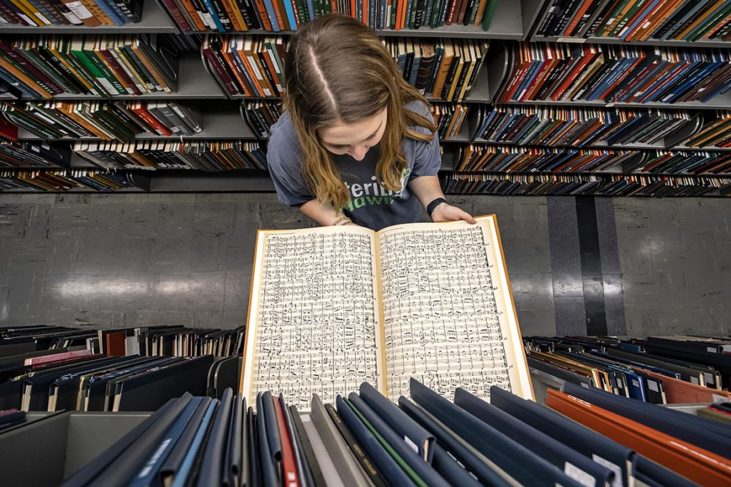 Student examines an open score amidst the music library stacks