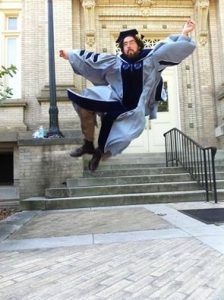Christi Jay Wells leaps in the air doing a heel click in full graduation regalia in front of the Hill Hall.